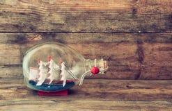 Bild des dekorativen Bootes in der Flasche auf Holztisch Verrostete, alte, symbolische Kette von einem Anker mit Booten verblaßte Stockbilder