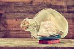 Bild des dekorativen Bootes in der Flasche auf Holztisch Verrostete, alte, symbolische Kette von einem Anker mit Booten verblaßte Lizenzfreies Stockbild