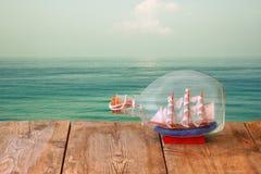Bild des dekorativen Bootes in der Flasche auf Holztisch vor Meer Verrostete, alte, symbolische Kette von einem Anker mit Booten  Lizenzfreie Stockbilder