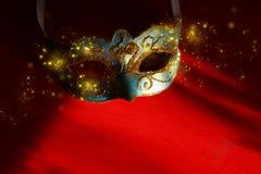 Bild des eleganten Blaus und des Goldes venetianisch, Karnevalmaske über rotem Hintergrund Magisches Funkeln ovrlay stockfotografie