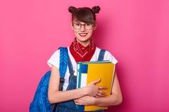 Bild des entzückenden lächelnden Schulmädchens hält bunte Mappen lokalisiert auf rosigem Hintergrund Junges Mädchen mit dem glück stockbilder