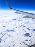 Bild des Flügels des Flugzeuges, Wolken, blauer Himmel vom Fenster Lizenzfreie Stockfotografie