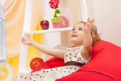 Bild des fröhlichen schönen Kindes, das auf Osmanen aufwirft Stockfoto