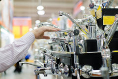 Bild des Geschäftsmann- oder Frauenwählens und rührender Hahnkran- oder -wasserhahn auf Einkaufsregalanzeige von DIY-Kaufhaus Stockfotografie