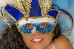 Bild des Gesichtes einer lächelnden Frau mit dem schwarzen gelockten Haar, das eine venetianische Maske trägt stockfotos