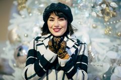 Bild des glücklichen Brunette auf Weg nahe bei verzierter weißer Fichte lizenzfreie stockfotos