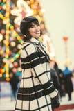Bild des glücklichen Brunette, unscharfer Hintergrund mit brennender Girlande lizenzfreie stockbilder