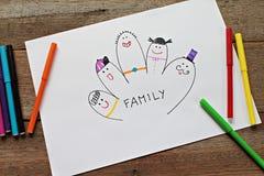 Bild des glücklichen Familienfingers auf Weißbuch und der bunten magischen Stifte auf hölzernem Hintergrund Stockfoto