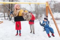 Bild des glücklichen Mädchens und des Jungen, die im Winter im Park mit Eltern schwingt Lizenzfreie Stockfotos