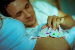 Bild des glücklichen zukünftigen Vatis, der an Babyschuhe hält Lizenzfreies Stockbild