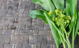 Bild des Grünkohl-Kantonesisch auf dem hölzernen Hintergrund stockbilder