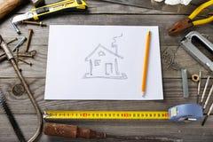 Bild des Hauses auf Blatt Papier mit alten Werkzeugen Stockfotos