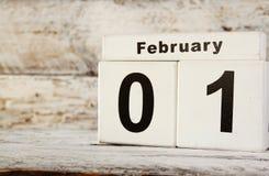 Bild des hölzernen Weinlesekalenders Februars erster auf weißem Hintergrund Stockbilder