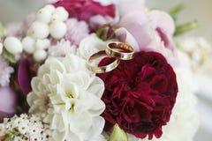 Bild des Hochzeitsblumenstraußes und -Eheringe auf ihm Lizenzfreie Stockfotos