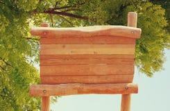 Bild des Holzschildes vor Bäumen am Wald lizenzfreie stockfotografie