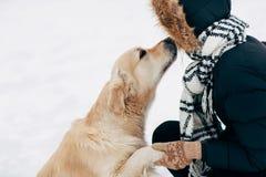 Bild des Hundes Tatze gebend der Frau in der schwarzen Jacke am Wintertag Stockbilder