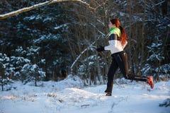 Bild des jungen Athleten laufend durch Winterwald Lizenzfreie Stockbilder