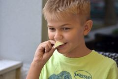 Bild des jungen blonden Jungen, der Stück Kartoffelchips schauen glücklich isst Lizenzfreie Stockbilder