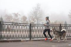 Bild des jungen Mädchens laufend mit ihrem Hund, alaskischer Malamute Lizenzfreies Stockbild