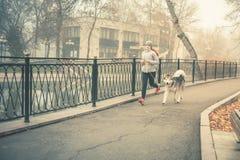 Bild des jungen Mädchens laufend mit ihrem Hund, alaskischer Malamute Stockfotografie