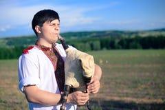Bild des jungen Mannes Rohre auf grünem Sommer spielend Lizenzfreies Stockbild