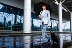 Bild des jungen redhaired Geschäftsmannes, der schwarzen Regenschirm und den Koffer gehend in Regen am Flughafen hält Stockfotografie