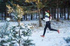 Bild des jungen weiblichen Athleten, der durch Winterwald läuft Lizenzfreie Stockfotos