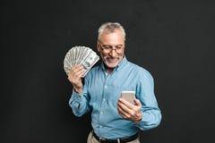 Bild des kaukasischen älteren Mannes 70s mit dem grauen Haar, das Mobile hält Lizenzfreies Stockfoto