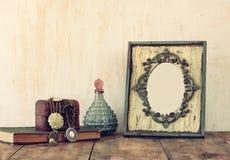 Bild des klassischen Rahmens, des Schmucks und der Parfümflaschen der Victorianweinleseantike auf Holztisch Gefiltertes Bild Lizenzfreie Stockfotografie