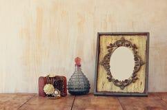 Bild des klassischen Rahmens, des Schmucks und der Parfümflaschen der Victorianweinleseantike auf Holztisch Gefiltertes Bild Lizenzfreies Stockbild