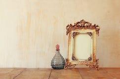 Bild des klassischen Rahmens und der Parfümflaschen der Victorianweinleseantike auf Holztisch Gefiltertes Bild Stockfoto