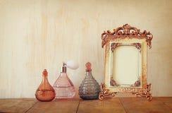 Bild des klassischen Rahmens und der Parfümflaschen der Victorianweinleseantike auf Holztisch Gefiltertes Bild Stockfotos