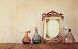 Bild des klassischen Rahmens und der Parfümflaschen der Victorianweinleseantike auf Holztisch Gefiltertes Bild Lizenzfreies Stockfoto