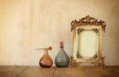 Bild des klassischen Rahmens und der Parfümflaschen der Victorianweinleseantike auf Holztisch Gefiltertes Bild Lizenzfreie Stockfotografie