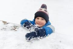 Bild des kleinen Jungen im Schnee auf Park Stockfotografie