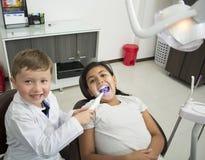 Bild des kleinen Mädchens, das Zähne überprüfen lässt Stockfoto