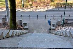Bild des konkreten Steins tritt das Treppenhaus, das unten zur Straße mit Ansicht des Parks im Hintergrund geht Stockfotos