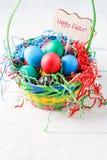 Bild des Korbes mit bunten Eiern auf leerem blauem Hintergrund auf Holztisch Stockbild