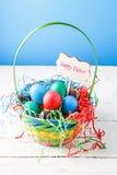 Bild des Korbes mit bunten Eiern auf leerem blauem Hintergrund auf Holztisch Stockfotografie