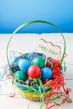 Bild des Korbes mit bunten Eiern auf leerem blauem Hintergrund auf Holztisch Stockbilder