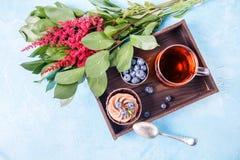 Bild des Kuchens, Blaubeere, rote Blumen Stockfotografie