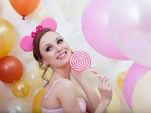 Bild des lächelnden comely Mädchens, das mit Lutscher aufwirft Lizenzfreies Stockfoto