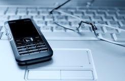 Bild des Laptops mit Gläsern und Mobiltelefon Stockfotos