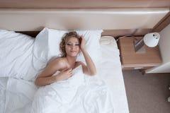 Bild des lächelnden geweckten Mädchens, das im Bett liegt Stockfotos