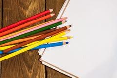 Bild des leeren Papiers und der bunten Bleistifte auf altem Holztisch Stockbild