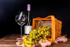 Bild des leeren Weinglases, Trauben des Grüns auf hölzernem Korb auf Tabelle Stockfotos