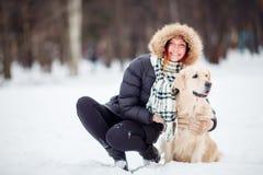 Bild des Mädchens in der schwarzen Jacke hockend nahe bei Hund im Winter Lizenzfreie Stockfotos