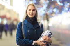 Bild des Mädchens im Mantel mit Geschenk im Kasten Lizenzfreie Stockfotos