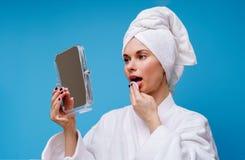 Bild des M?dchens im wei?en Mantel und im Tuch auf ihrem Kopf mit Baumwollauflage und -spiegel in ihrer Hand stockbilder