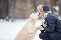 Bild des Mädchens Labrador im schneebedeckten Park umarmend Lizenzfreie Stockfotos